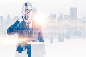 The double exposure image of the businessman using a smartphone during sunrise overlay with cityscape image. The concept of modern life, business, city life and internet of things.