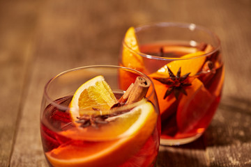 close up view of mulled wine in glasses with orange pieces and spices on wooden tabletop