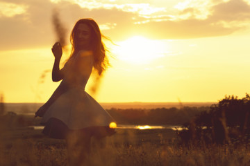silhouette of a dreamy girl in a field at sunset, a young woman enjoying nature