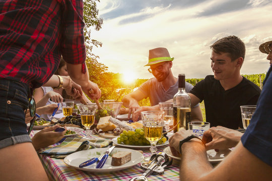 happy best friends have an al fresco party in the garden. they enjoy a meal of simple food with fresh white wine.