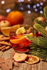 close up view of tasty mulled wine drink with orange pieces and spices on wooden surface with bokeh lights on backdrop