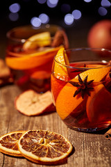 close up view of delicious hot mulled wine drinks and spices on wooden tabletop with blurred bokeh lights on background