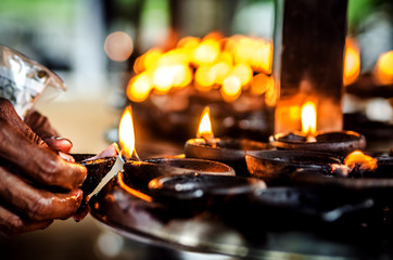 The believer lights a candle in a Buddhist temple. Sri Lanka.