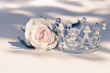 Kleine Krone mit Perlen und einer Rose mit Licht und Schatten festliche Dekoration