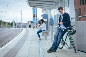 Businessman leaning against bicycle and using mobile phone