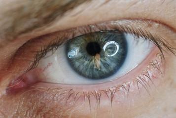 Blue man eye with contact lens, macro shot. Shallow depth of field.