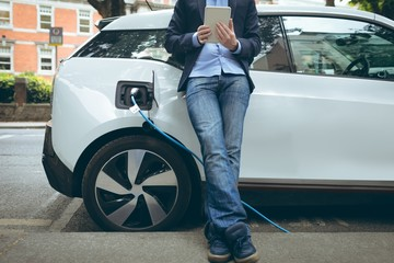 Businessman using digital tablet while charging electric car at