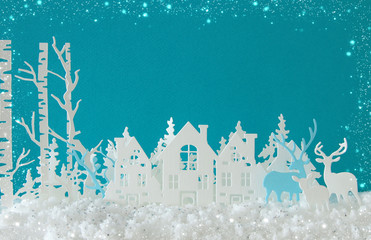 Magical Christmas paper cut winter background landscape with houses, trees, deer and snow in front of turquoise background.