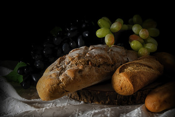variety kind of bread on wooden plank with white and red grape in dark tone background