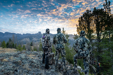Three adult male hunter friends, unrecognizable,  stand on a mountain ridge looking for elk to hunt during bow archery season. Wearing camouflage Wall mural