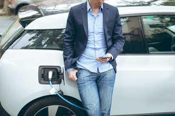 Businessman using mobile phone while charging electric car at