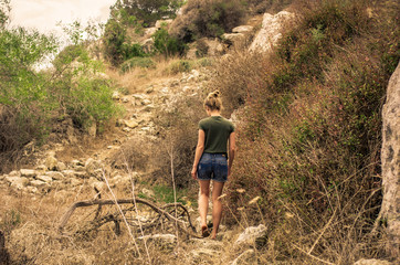 A woman in the summer walks uphill overcoming obstacles from stones and shrubs