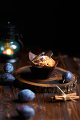 blueberry muffin cupcake on a dark wooden background with plums