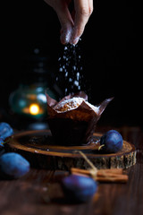 Female hands sprinkled with blueberry muffin with powdered sugar on a dark wooden background with plums.