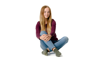 Young teen girl sitting on white background