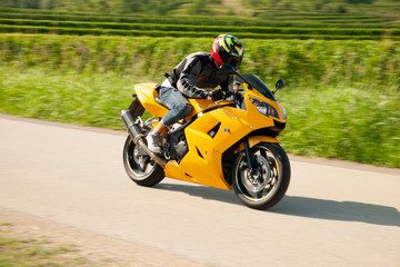 Man drive a motorbike on a country road with vineyards in background