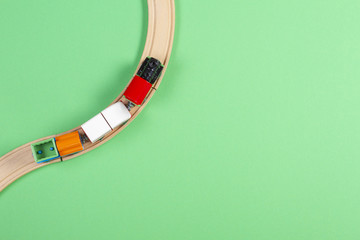 Toy train and wooden rails on green background Wall mural