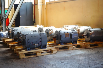 The electric motors are on a rack in a warehouse, in production.