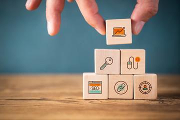 Hand stapelt Online-Marketing Komponenten als Symbole auf Würfeln