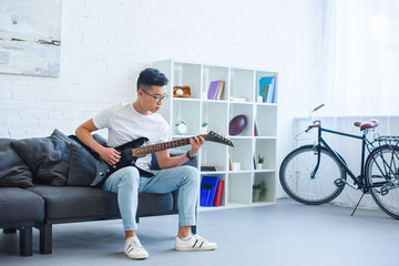 handsome asian man playing black electric guitar on sofa at home