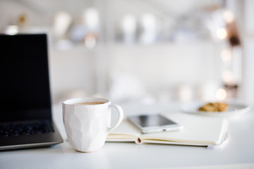 Modern white office, designer handmade cup with coffee, smartpho