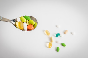 Various colorful pills on spoon