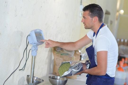 processed food worker weighing green-peas