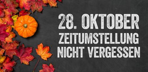 Herbstlaub mit Kürbis auf einem dunklen Hintergrund - Zeitumstellung nicht vergessen
