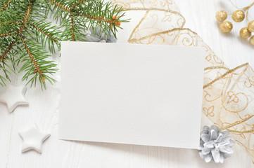 Empty white sheet of paper on a white Christmas background of fir branches and cones. Letter on xmas, mockup