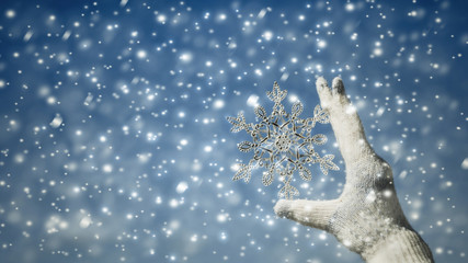 Female hands in a knitted gloves with sparkling huge snowflake on the winter snowfall background. Winter and Christmas concept.