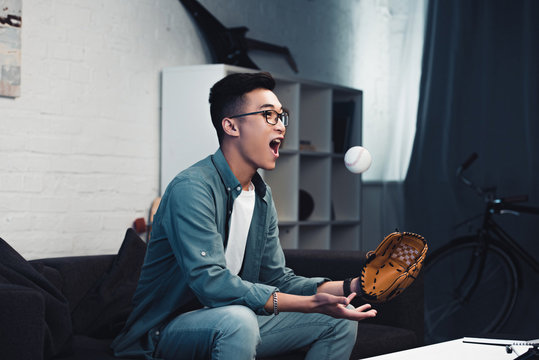 emotional young asian man with baseball glove and ball sitting on couch and watching sport match at home