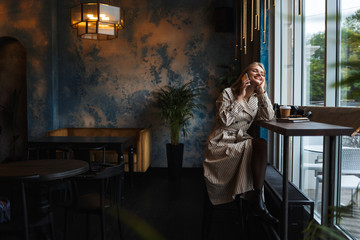 Young attractive woman in striped trench coat happily talking on cellphone sitting near big window while spending time in modern cafe