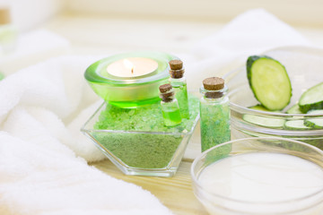 Cucumber home spa and hair care concept. Sliced cucumber, bottles of oil, sea salt, bathroom towel. White board background