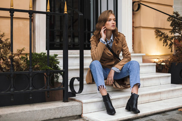 Pretty girl in trench coat and jeans thoughtfully looking aside sitting on little stairs while spending time on cozy city street