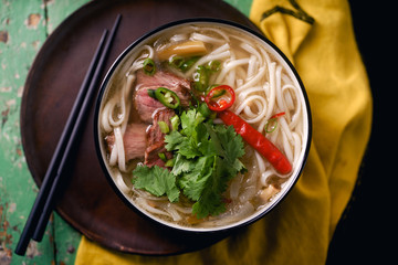Vietnamese traditional soup Pho Bo with beef and fresh coriander on rustic wooden table