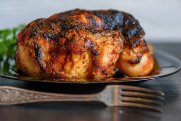 baked chicken on a dark wooden background.
