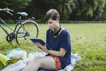 Young adult woman reading an ebook at a public park
