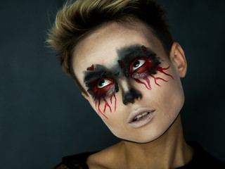 Makeup for Halloween. Portrait of a girl with bleeding eyes.