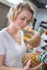 woman choosing fruits at supermarket and holding pineapple