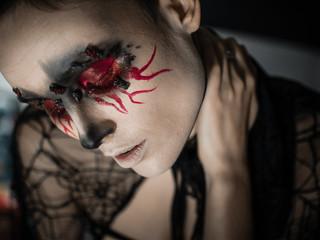 Portrait of a female vampire over black background