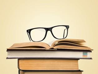 Black glasses on open books