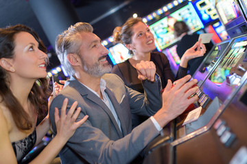 People in casino excitedly watching slot machine