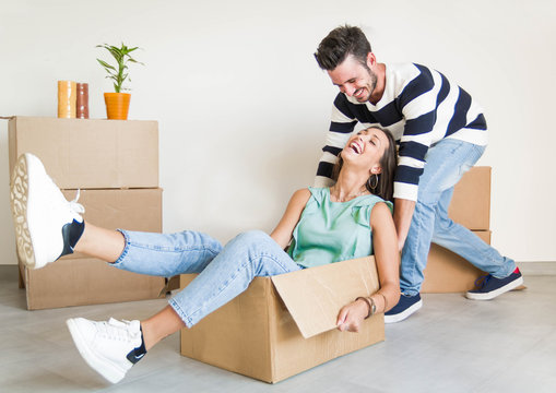 Happy couple in love having fun unboxing cardboards moving in the new house