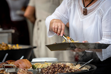 Latvian national cuisine. A woman puts hot dishes from a large pan.