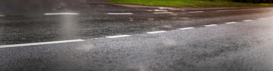 Wall Mural - wet black asphalt road and white dividing lines