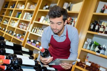 man seller wearing uniform using a tablet in wine house