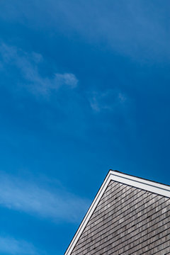 A blue sky with wispy clouds stands about a peaked roof with a wooden shake shingle siding. This is a vertical image.