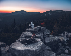 Man and dog sitting on rock during sunset