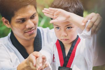 Taekwondo master black belt teaching kid to fight guard