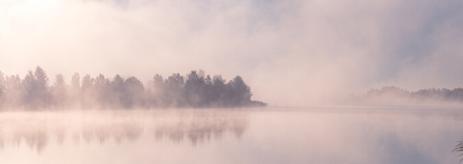 Beautiful foggy morning. Fog over autumn lake at sunrise moment. Wide panorama.